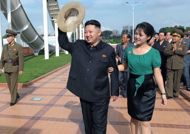 North Korean leader Kim Jong Un, center, accompanied by his wife Ri Sol Ju, right, waves to the crowd as they inspect the Rungna People's Pleasure Ground in Pyongyang