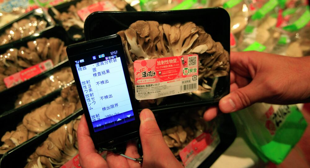 Tokyo market, a smartphone shows a list of types and amounts of radiation on a package of Maitake mushrooms which is part of a radiation sampling test