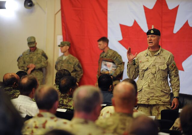 Brigadier General Dean Milner, Commander of Canadian forces in Afghanistan, speaks with soldiers after a handover ceremony to US forces at Kandahar airbase