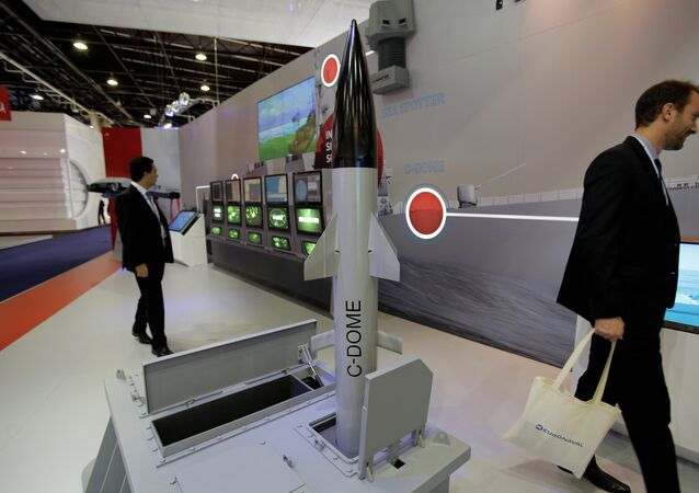 Visitors walk past a model of Israeli weapon company Rafael' C-Dome is presented at the Euronaval show, in Le Bourget, north of Paris.