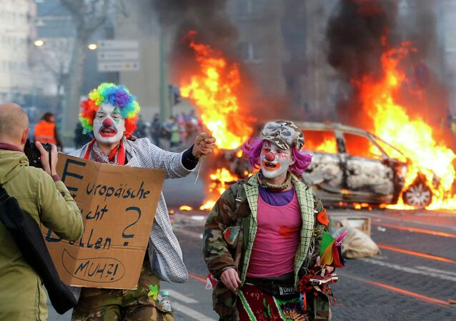 Demonstrators dressed as clowns pass by a burning police car Wednesday, March 18, 2015 in Frankfurt, Germany.