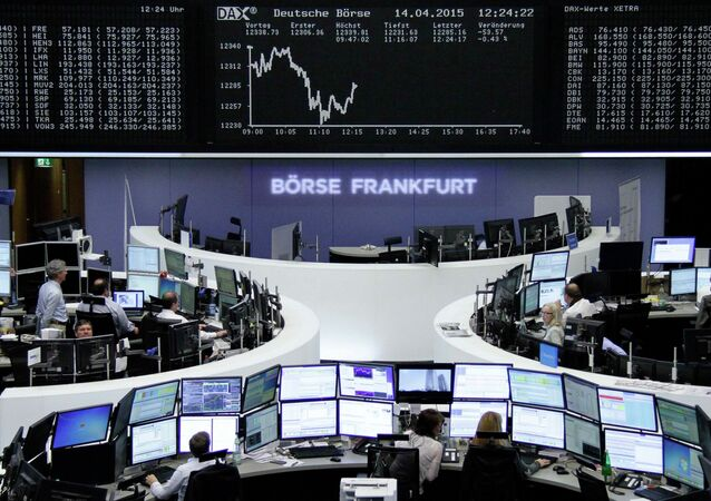 Traders are pictured at their desks in front of the DAX board at the Frankfurt stock exchange April 14, 2015