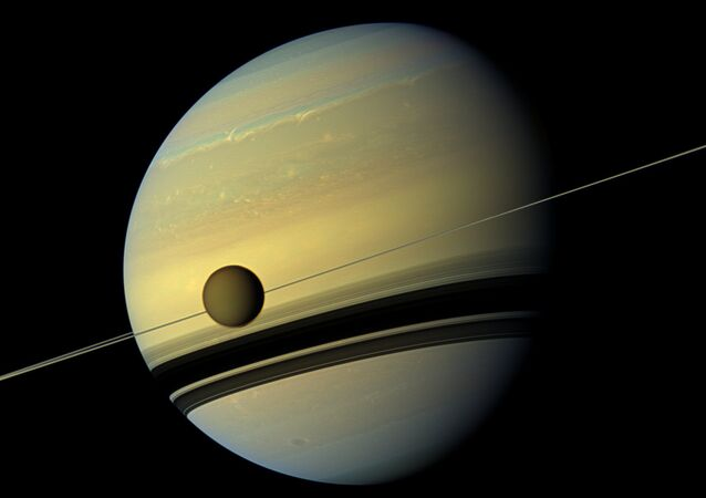 Saturn's largest moon Titan passing in front of the giant planet in an image made by NASA's Cassini spacecraft