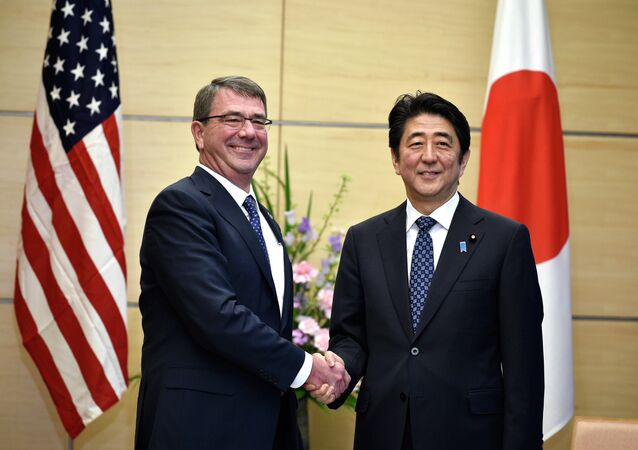 U.S. Defense Secretary Ash Carter, left, shakes hands with Japan's Prime Minister Shinzo Abe at the start of their meeting at Abe's official residence in Tokyo.
