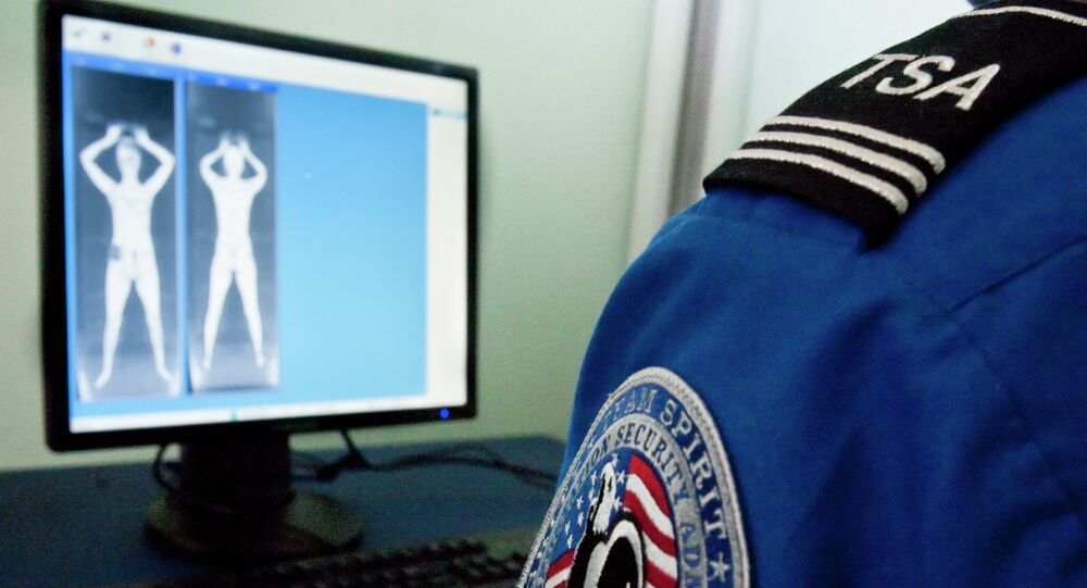 A TSA officer looks at a simulated image from a new backscatter X-ray machine