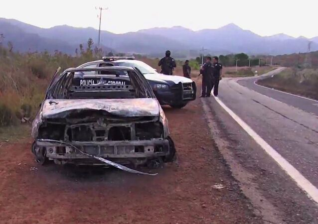 Grab taken from a video of policemen inspecting a burnt police vehicle on April 7, 2015 on a Jalisco state road, Mexico, where at least 15 police officers were killed, overnight, in an ambush carried out by a gang called Jalisco New Generation Drug Cartel.