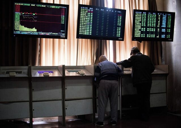 Chinese investors look at prices of shares and the Shanghai Composite Index at a stock brokerage house in Shanghai on April 15, 2015