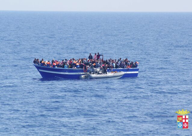 Italian Navy on Sunday, June 15, 2014, and taken on Saturday, June 14, 2014, a boat filled with migrants receives aid from an Italian Navy motor boat off the coast of Sicily, Italy. The Italian coast guard and navy have rescued more than 300 migrants.