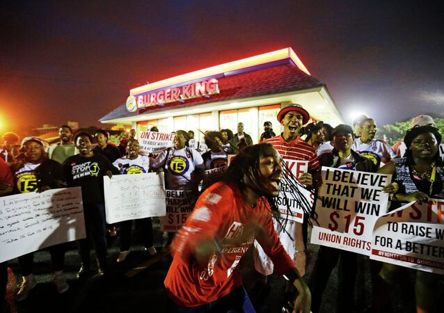 Joshua Collins, center, chants during a protest outside a Burger King restaurant by fast-food workers and activists calling for the federal minimum wage to be raised to $15, Wednesday, April 15, 2015, in College Park, Ga. Organizers say they chose April 15, tax day, to demonstrate because they want the public to know that many low-wage workers must rely on public assistance to make ends meet.
