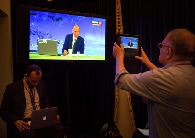A journalist takes a picture from a TV screen while Russian President Vladimir Putin speaks during a nationally televised question-and-answer session in Moscow in Moscow, Russia, Thursday, April 16, 2015