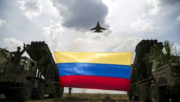 A Russian-made Sukhoi Su-30MKV fighter jet of the Venezuelan Air Force flies over a Venezuelan flag tied to missile launchers, during the Escudo Soberano 2015 (Sovereign Shield 2015) military exercise in San Carlos del Meta in the state of Apure - Sputnik International