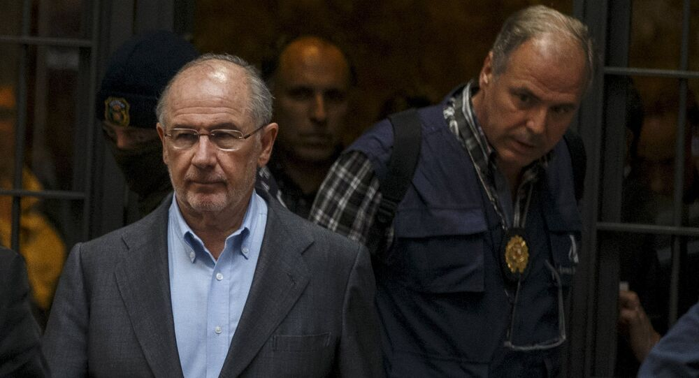 Rodrigo Rato (L), former People's Party minister and former managing director of the International Monetary Fund, is lead by police as they leave his residence after an inspection in Madrid