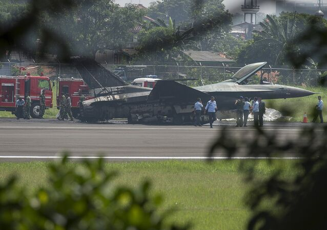 Air Force personnel stand near an Indonesian F-16 plane after it burned following an aborted take-off at Halim Air Base, East Jakarta April 16, 2015