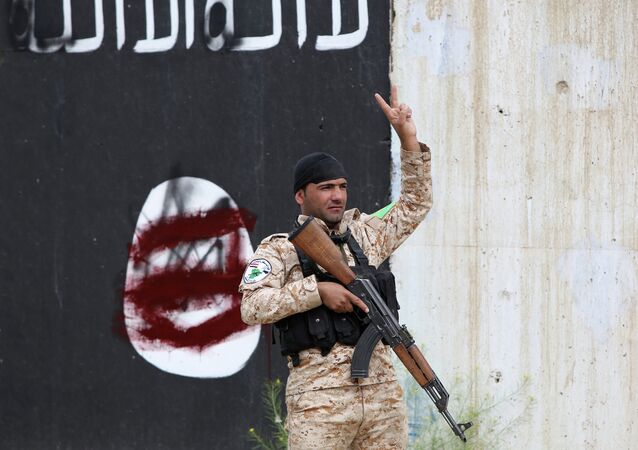 A member of the Iraqi security forces flashes the sign for victory in front of a defaced Islamist flag in Tikrit