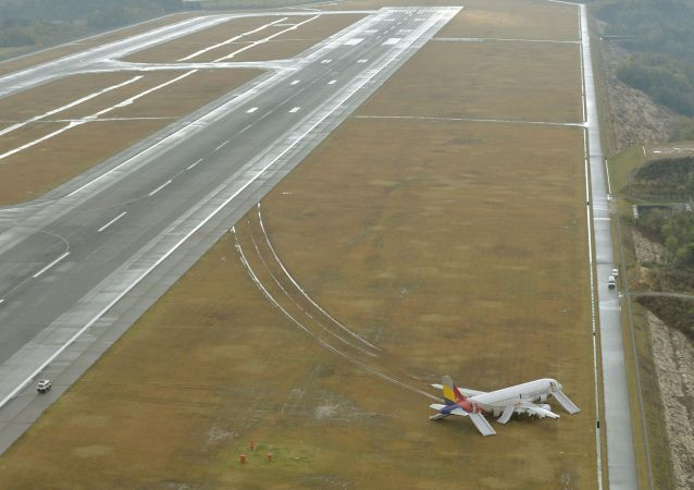 An aerial view shows an Asiana Airlines airplane which ran out of runway after landing at Hiroshima airport in Mihara, Hiroshima prefecture, western Japan, in this photo taken by Kyodo April 15, 2015.