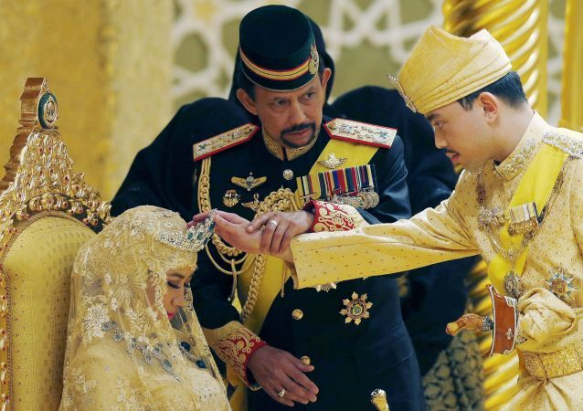 Brunei's Sultan Hassanal Bolkiah holds the arm of his son Prince Abdul Malik to bless Malik's new wife Dayangku Raabi'atul 'Adawiyyah Pengiran Haji Bolkiah