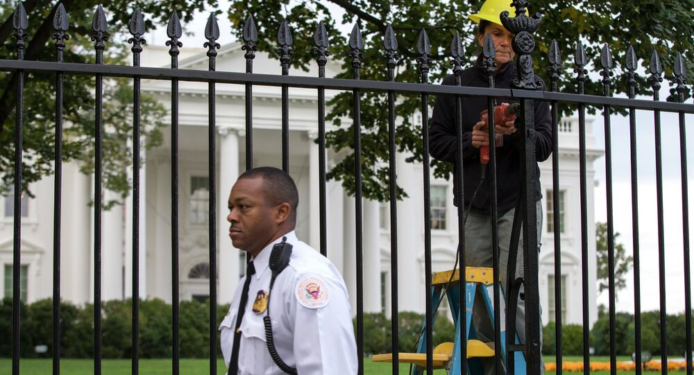 A Secret Service police officer walks outside the White House in Washington, Thursday, Oct. 23, 2014, as a maintenance worker performs fence repairs as part of a previous fence restoration project.