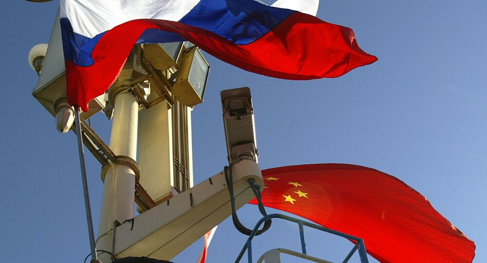 A worker places the Russian and Chinese flags outside Tiananmen Gate
