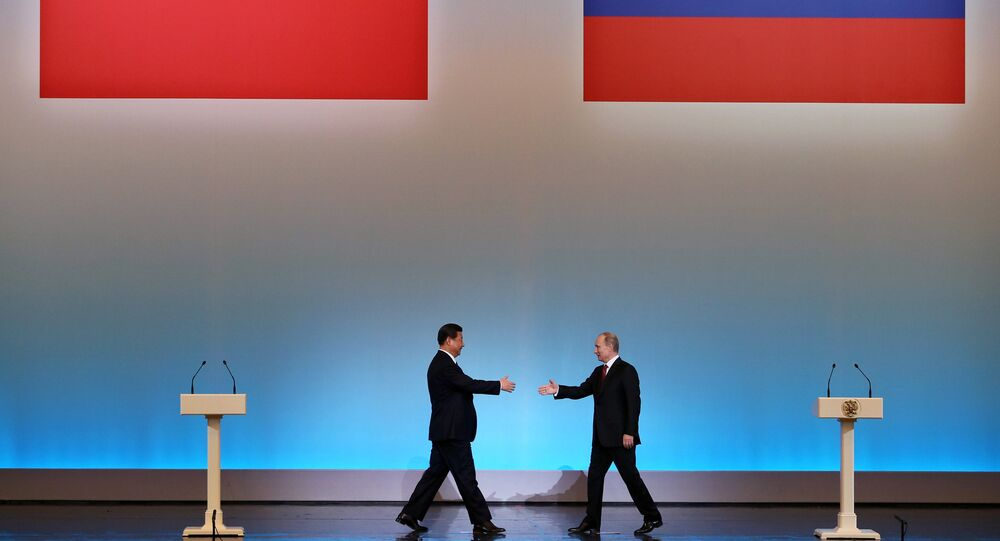 China's President Xi Jinping (L) is welcomed by his Russian counterpart Vladimir Putin (R) during the opening ceremony of The Year of Chinese Tourism in Russia in Moscow