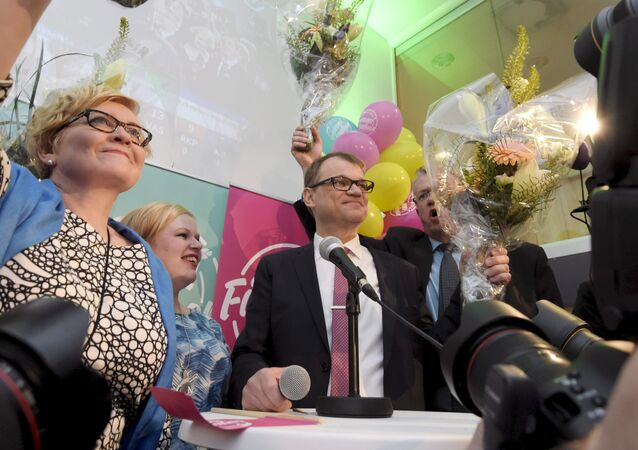 Anu Vehvilainen (L), Annika Saarikko, Chairman Juha Sipila and Juha Rehula of the Centre Party celebrate at the party's parliamentary elections reception in Helsinki after the results of the votes