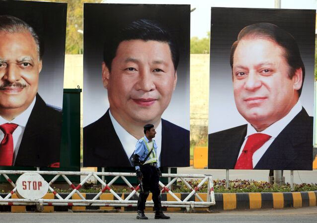 A policeman stands guard next to giant portraits of (L-R) Pakistan's President Mamnoon Hussain, China's President Xi Jinping, and Pakistan's Prime Minister Nawaz Sharif, displayed along a road ahead of Xi's visit to Islamabad