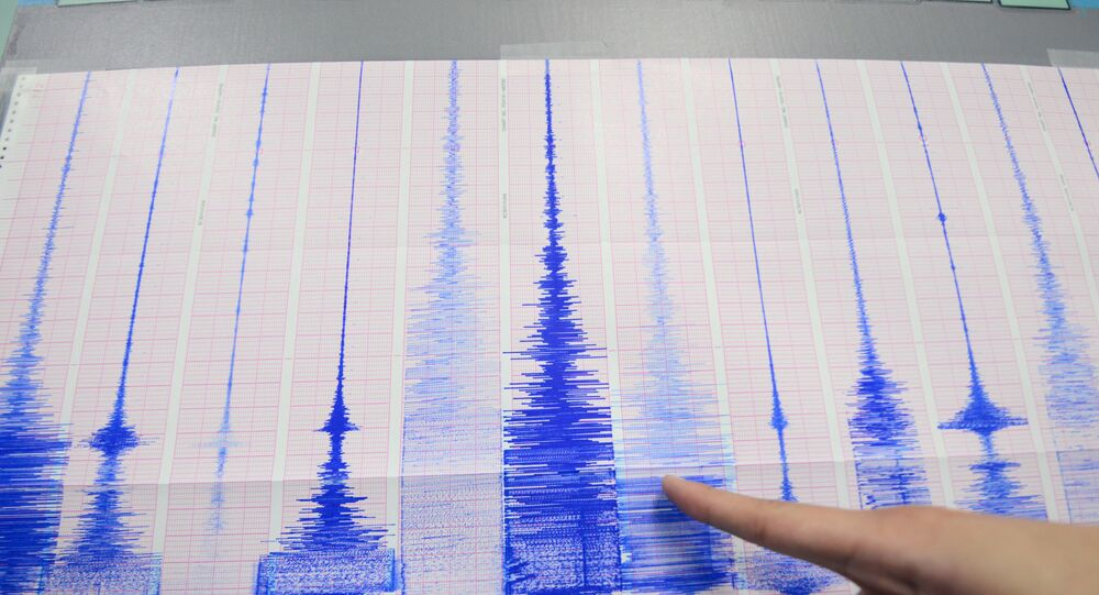 A staff member of the Seismology Center points to a chart showing the earthquake activity