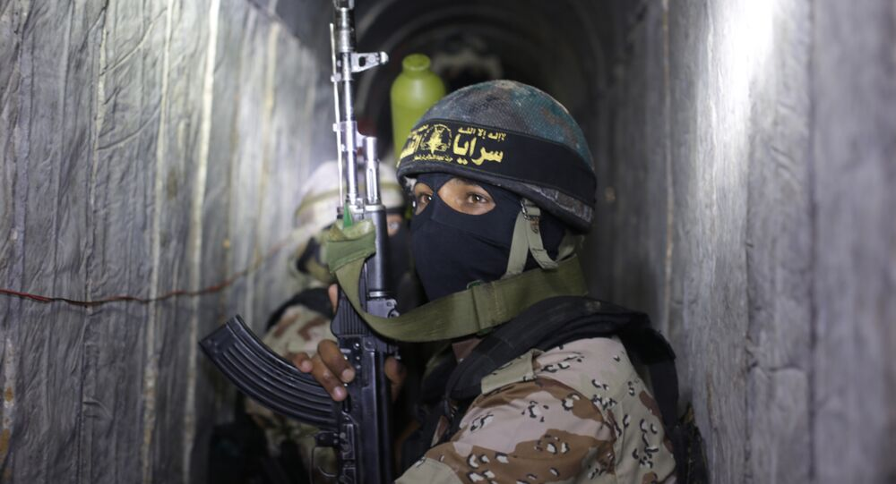 Palestinian militants from the Islamic Jihad's armed wing, the Al-Quds Brigades, squat in a tunnel, used for storing weapons, as they take part in military training in the south of the Gaza Strip on March 3, 2015.