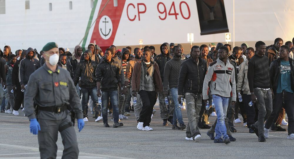 Migrants are disembarked from a Coast Guard boat in the Sicilian harbour of Augusta