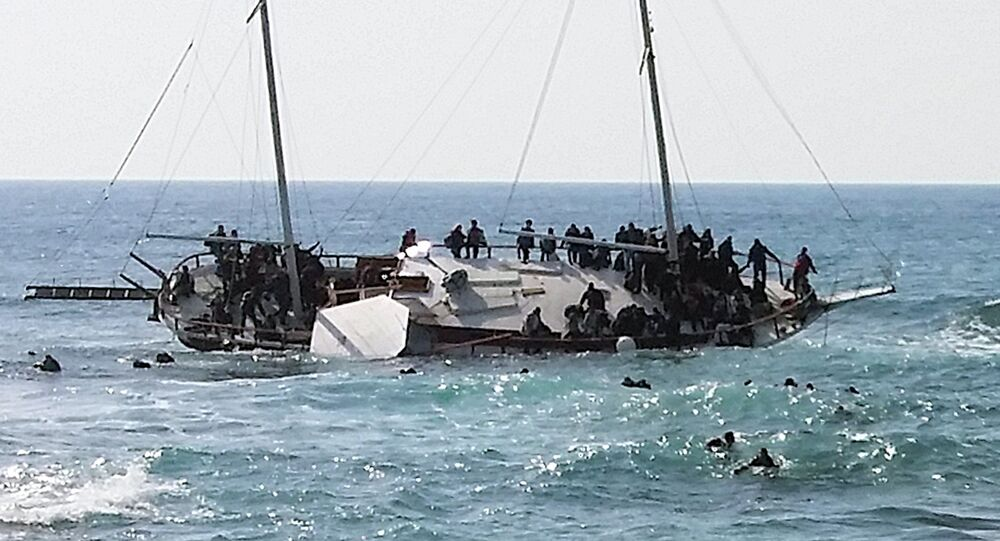Migrants, who are trying to reach Greece, are seen onboard a capsized sailboat, as others are seen in the water trying to reach the coast of the southeastern island of Rhodes April 20, 2015