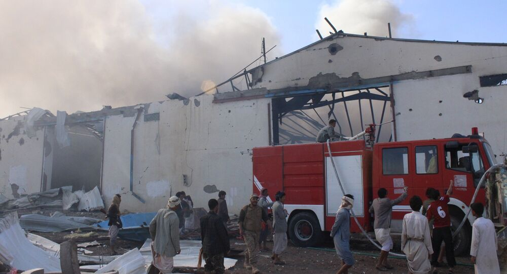 Civil defence workers try to put out the fire caused by an air strike on a food stuff depot in Yemen's northwestern city of Saada April 18, 2015