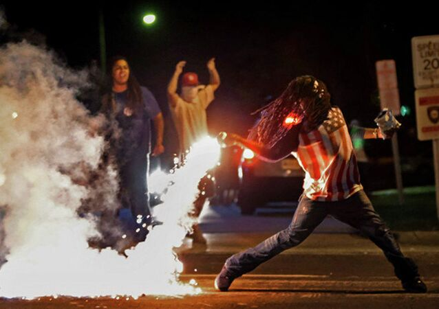 This August 13, 2014, photo by St. Louis Post Dispatch photographer Robert Cohen shows Edward Crawford returning a tear gas canister fired by police who were trying to disperse protesters in Ferguson, Missouri