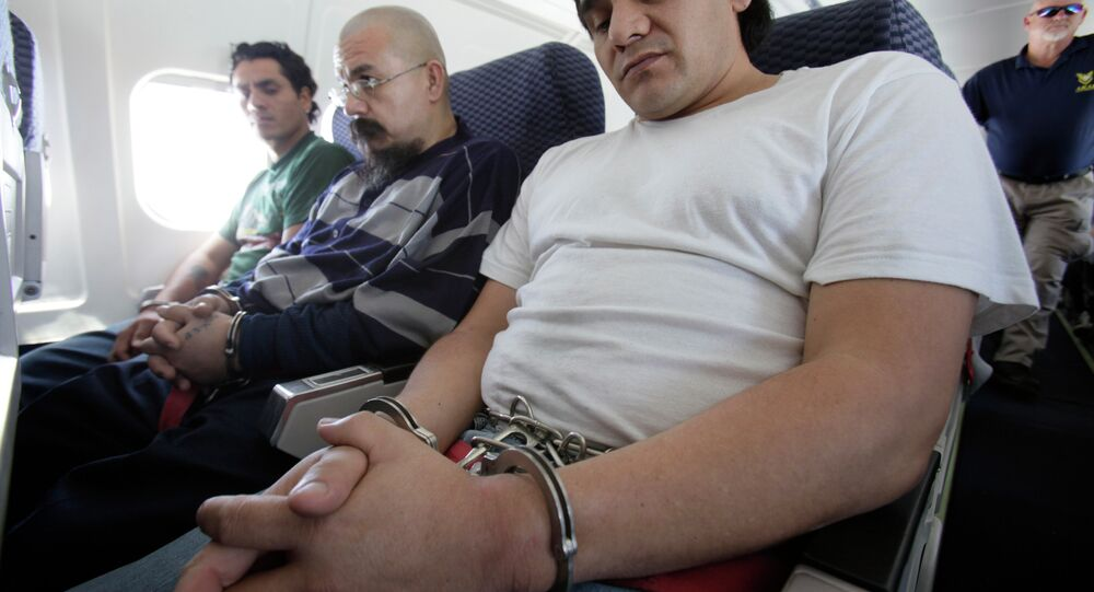 Shackled Mexican immigrants sit aboard a deportation jet charted by the US Immigration and Customs Enforcement.