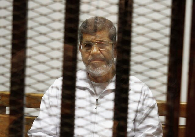 Egypt's ousted Islamist President Mohammed Morsi sits in a defendant cage in the Police Academy courthouse in Cairo, Egypt. On Tuesday April 21, 2015, an Egyptian criminal court sentenced Morsi to 20 years in prison over the killing of protesters in 2012, the first verdict to be issued against the leader. The case stems from violence outside the presidential palace in December 2012.