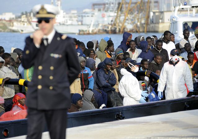 Migrants wait to disembark from a tug boat in the Sicilian harbour of Trapani, April 17, 2015