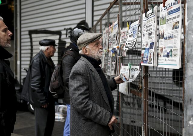 People read newspaper headlines in Athens March 23, 201