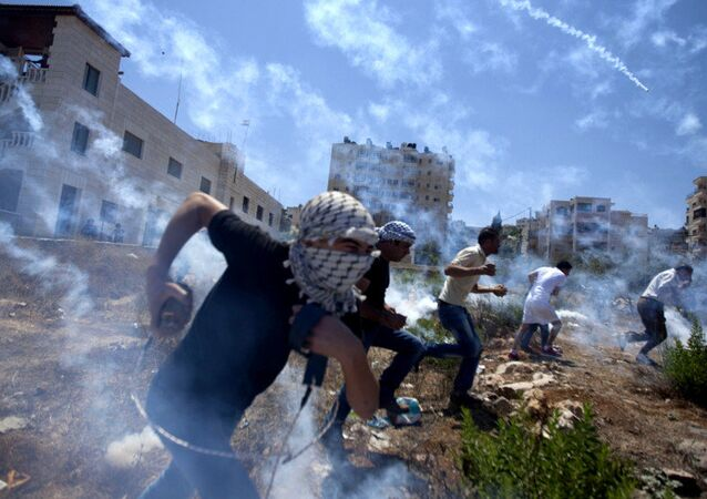 Palestinians run for cover during clashes with Israeli soldiers following a protest against the war in the Gaza Strip in August 2014.