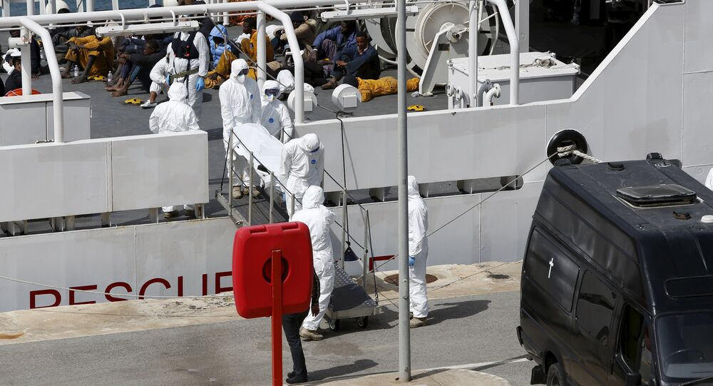 Armed Forces of Malta personnel in protective clothing carry the body of a dead immigrant off Italian coastguard ship Bruno Gregoretti as surviving migrants watch in Senglea, in Valletta's Grand Harbour, April 20, 2015