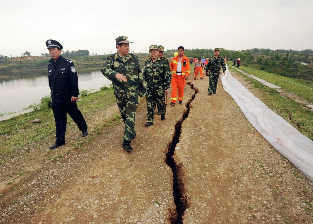 In this photo released by China's Xinhua News Agency, rescuers inspect a crack at Fengshou reservoir dam, caused by Monday's 7.9 magnitude earthquake in Anxian County, southwest China's Sichuan Province, in May 2008.