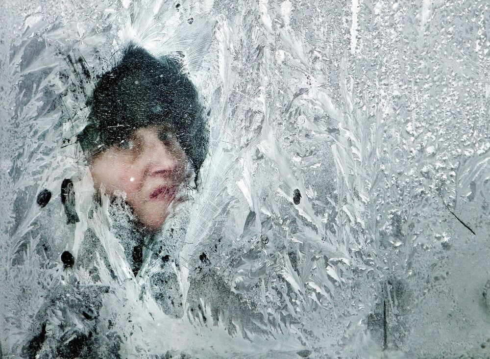 A woman looks out of a window covered in frost on a bus in Bucharest, Romania, in February 2012