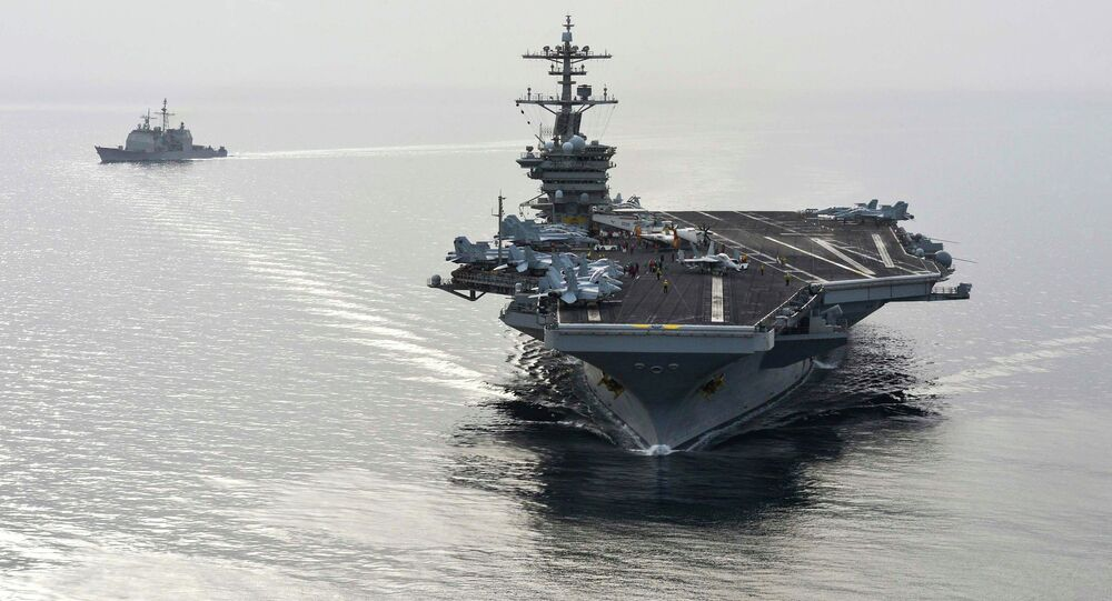 The aircraft carrier USS Theodore Roosevelt (CVN 71) and the guided-missile cruiser USS Normandy (CG) 60 sail in the Arabian Sea, in this U.S. Navy photo taken April 16, 2015