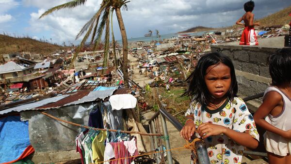 Filipino children play as houses damaged by Typhoon Haiyan are seen in the background in Marabut, Philippines in 2013. - Sputnik International