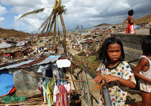 Filipino children play as houses damaged by Typhoon Haiyan are seen in the background in Marabut, Philippines in 2013.