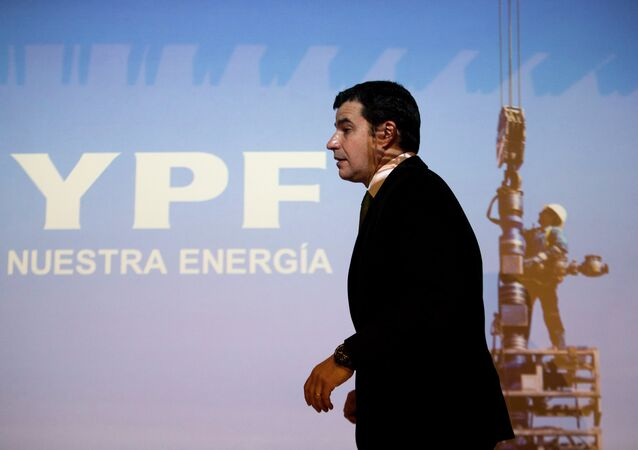 Miguel Galuccio, CEO of Argentina's state-controlled YPF oil company, walks in front of a screen during a joint news conference with Ali Moshiri, Chevron's head of Latin America, Middle East and Africa, in Buenos Aires, Argentina, Thursday, Aug. 29, 2013