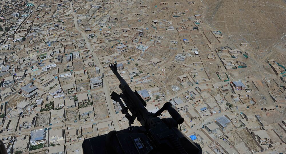 Residential houses and a mounted machine gun manned by an Afghan National Army soldier is pictured during a helicopter flight