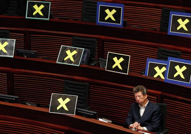 Pro-democracy lawmaker Ronny Tong sits with placards of yellow crosses placed after the lawmakers walk out of the legislative chamber to protest against Chief Secretary Carrie Lam who unveiled the Beijing-backed election reform package's details, in Hong Kong