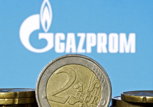Euro coins are seen in front of displayed logo of Gazprom