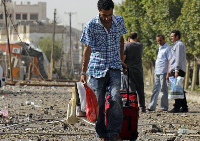 A man carries his belongings on a street of Sanaa.