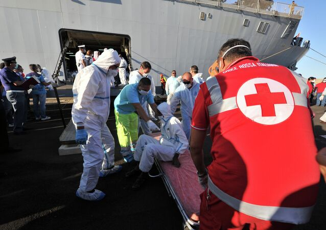 Rescuers take care of an immigrant, part of a group of more than 1,370 people, after he disembarked from the Italian military ship San Giusto on August 25, 2014 in the port of Crotone, southern Italy, following the Mare Nostrum rescue operations at sea