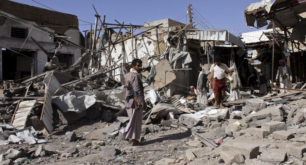 People inspect the site of an air strike in Yemen's northwestern city of Saada April 22, 2015