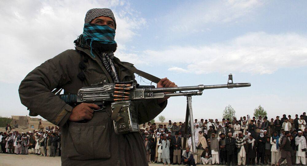 A member of the Taliban insurgent and other people stand at the site during the execution of three men in Ghazni Province on April 18, 2015.